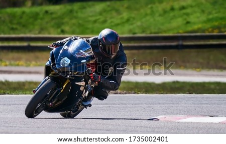 Motorcycle practice leaning into a fast corner on track. Sport Biker Racing on Road Stock photo ©