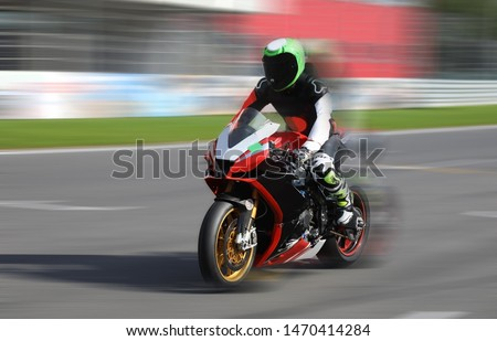 Motorcycle racer in helmet and gear at high speed racing on the race track