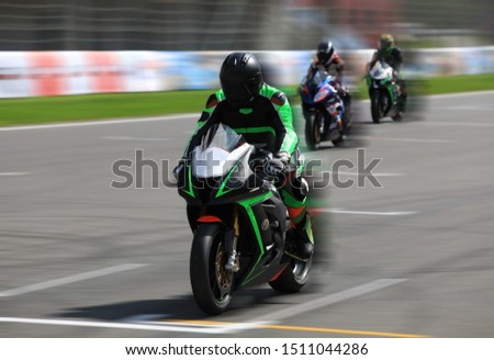 Motorcycle racers compete at high speed on the race track #1511044286