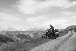 Motorcycle rider enjoy the momment. Touring adventure motorbike on the top of mountain, enduro, off road, beautiful view, black and white, freedom, extreme vacation. Copy space. Passo Pordoi, Italy