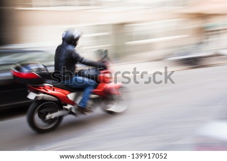 motorcycle rider in the city traffic in motion blur
