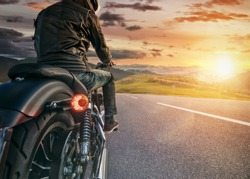 Motorcycle rider ready for drive in Alps, beautiful sunset dramatic sky. Travel and freedom, outdoor activities