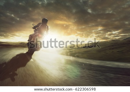 Motorcycle rides through a curve at sunset