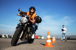 Motorcycle school of driving. Female driver with helmet taking motorcycle lessons and practicing ride. In background traffic cones and instructor with checklist rating and evaluating the ride.