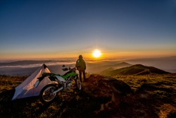 Motorcycle standing on a top of mountain under a blue sky on a background of mountains and sunrise