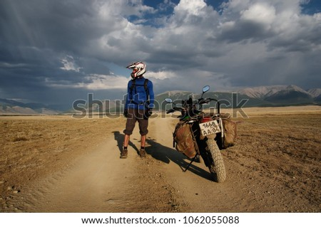 Motorcycle traveler man in helmet with suitcases standing on extreme rocky road in a mountain valley in cloudy weather on the background of endless steppe #1062055088