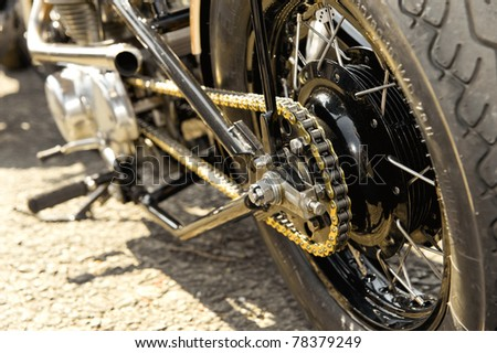 motorcycle wheel and drive-chain with golden toned highlights