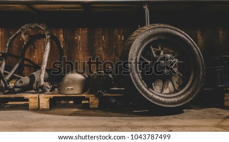 Motorcycle wheel on the floor with workshop tools, vintage garage, with blank copy space  #1043787499