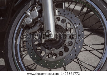 Motorcycle wheel with disk brakes system and metal spokes. Close up detailed photo of motorbike forks and tire. Different parts of two-wheeled vehicle. Transportation. Modern driving technologies. #1427691773