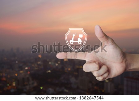 Motorcycle with shield flat icon on finger over blur of cityscape on warm light sundown, Business motorbike insurance concept #1382647544