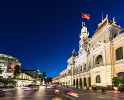 Motorcycles rushing at night in front of the famous People's Committee Building in the heart of Ho Chi Minh downtown district in Vietnam largest city, aka Saigon.