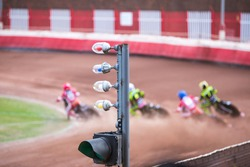 Motorcycles speedway race, four motorbikes in the curve, focus on foreground