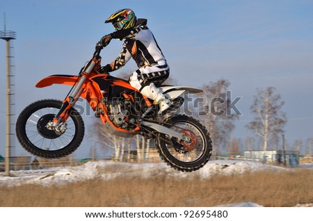 Motorcycling in the winter, a rider on a bicycle moto-cross flies over the hill on a snowy road, shot from the left side