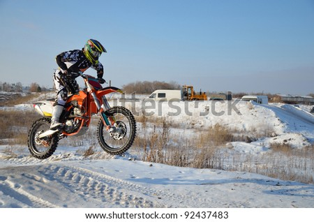 Motorcycling rider on a motorcycle motocross jumps from a hill on a snowy highway