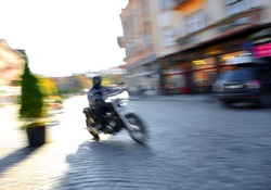 Motorcyclist in motion going down the street . Intentional motion blur
