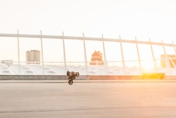 Motorcyclist makes a dangerous trick on the background of the sunset, riding on the rear wheel.Man rides a motorcycle on the background of a beautiful city landscape.Stuntman trains on a motorcycle.