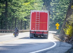 Motorcyclist on the bike overtaking a big rig industrial semi truck with red bulk semi trailer on the winding mountain road in prohibited no-overtaking zone without a secure road view