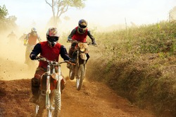 Motorcyclist on the competition at motorcycle race . The motorcycle race hole on December at Dambri waterfall, motorcyclist try to speed up goal, red soil way, indistinct dust