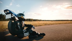 Motorcyclist or biker in black leather jacket and safety helmet sits near sports motorcycle on the road and looks at the sunset sky with copy space