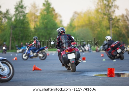 Motorcyclists ride through cones. Exersice for beginners and experienced. Free skill training as gymkhana for all people