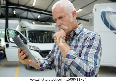 motorhome renting business manager looking at tablet #1508911784