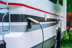 Motorhome stillife. Concept of power supply of the camper. Plug of the electric wire is inserted into the socket of the rv trailer.