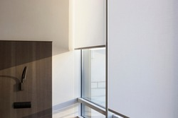 Motorized roller shades. Automatic roller blinds white color on large windows. Remote Control Shades are in the hotel. The sun's rays enter the room through the window. Wall lamp next to the window.
