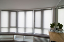 Motorized roller shades in the interior. Automatic roller blinds beige color on big glass windows. Home luxury curtaines are above the windosill with pillows. Summer. Green trees outside.
