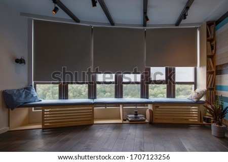 Motorized roller shades in the interior. Automatic roller blinds beige color on big glass windows. Remote Control Shades are above the windosill with pillows. Summer. Green trees outside. Foto stock ©