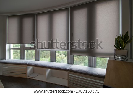 Motorized roller shades in the interior. Automatic roller blinds beige color on big glass windows. Home luxury curtaines are above the windosill with pillows. Summer. Green trees outside. Foto d'archivio ©