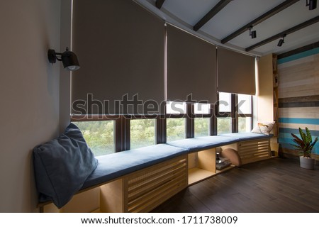 Photo of  Motorized roller shades in the interior. Automatic roller blinds beige color on big glass windows. Remote Control Shades are above the windosill with pillows. Summer. Green trees outside.
