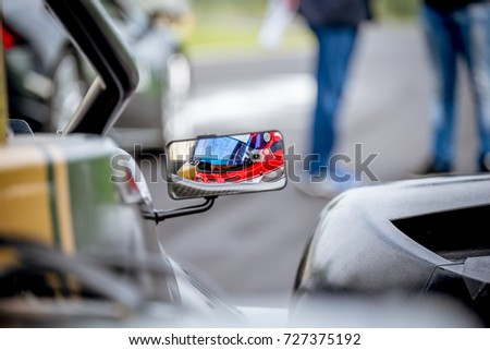 Motorsport car driver detail on rear view mirror before racing start on starting grid #727375192