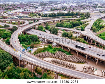 Motorway complex road junction aerial view with traffic moving in the UK. Cars, lorries, vans and a train can be seen travelling through a busy road interchange from above