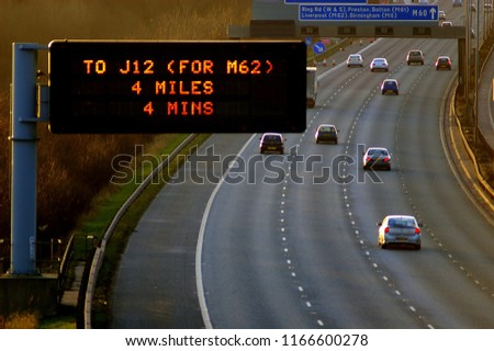 Motorway to Liverpool, with Matrix sign informing drivers of distance and time to a certain junction or exit #1166600278