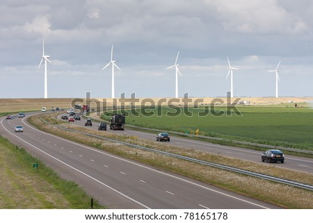 Motorway with a line of big windturbines behind it