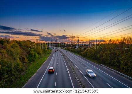 Motorway with blurry cars at sunset #1213433593