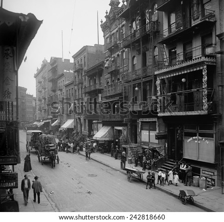 Mott Street in New York City's Chinatown presents a cosmopolitan scene mixing Asian and American-European dress and faces. The street is lined with restaurants, laundries, and pushcarts. Ca. 1900.