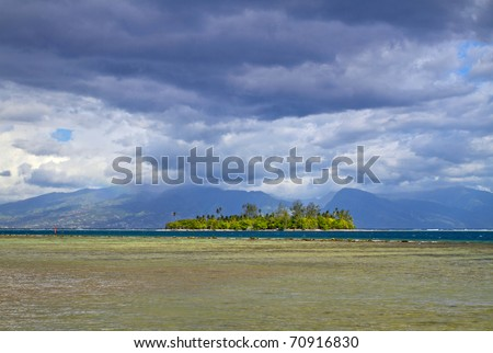 Motu is a small island on the reef, from Moorea island with Tahiti behind the clouds.
