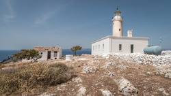 Moudari lighthouse with white painted building and shed under a blue sky at the island of Kythira in Greece