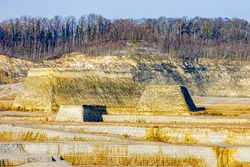 Mounds with a limestone stone hill with bare trees at the excavation site in the old marl mine at Sint-Pietersberg or Mount Saint Peter, part of the Caestert plateau in South Limburg, Netherlands