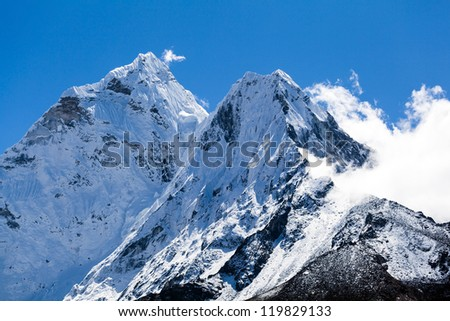 Mount Ama Dablam in Himalaya Mountains, Nepal. Beautiful landscape, summits in bright high mountains over blue sky.