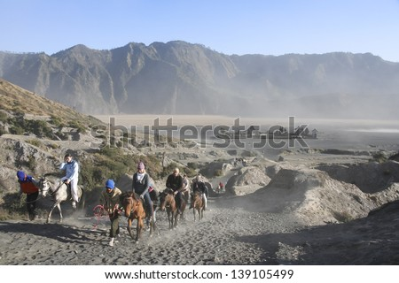 MOUNT BROMO, JAVA - SEPT 26: tourists on horses climbing the slopes of  mount bromo volcano on Sept 26 2007 in JAVA. The active Mount Bromo is one of the most visited tourist attractions in East Java,