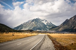 Mount Cook or Aoraki National park with road over the mountain and the cloudy sky in background