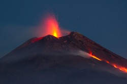 Mount Etna in eruption with lava flow at night. View from the Valle del Bove