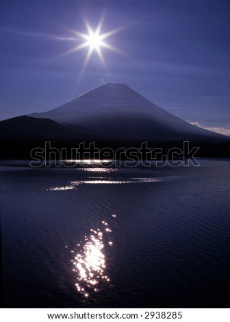 Mount Fuji with the Sun and its glittering reflections in a mountain lake