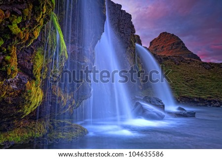 Mount Kirkjufell (Church mountain) in the Snaefellsnes peninsula, Iceland (Island), complimented by a waterfall on a beautiful summer evening