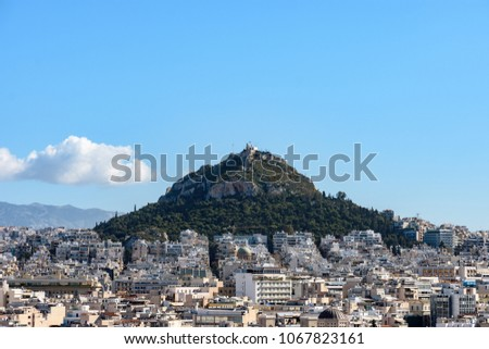 Mount Lycabettus surrounded by buildings with blue sky and white cloud as background in Athens, Greece during sunny daytime in the morning. #1067823161