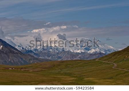 Mount McKinley peaks through dramatic clouds over lush green tundra in Denali National Park, Alaska.