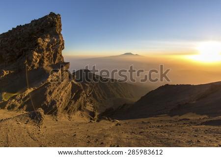 Mount Meru and Mt Kilimanjaro in the distance near Arusha in Tanzania. Africa. Mt Meru is located 60 kilometres west of Mount Kilimanjaro.