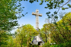 Mount Royal Cross surrounded by green trees and blue sky, sitting at the top of mount royal park in beautiful Montreal Quebec